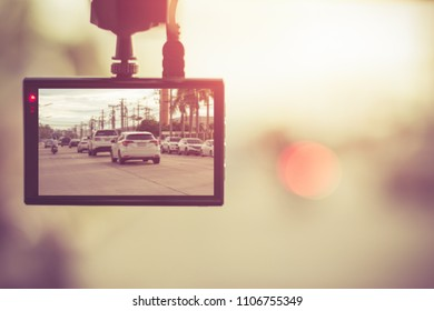 Close up car on highway at sunset, with video recorder next to a rear view mirror,video recorder driving a car on highway,car video recorder,Full HD camera recorder for vehicle.