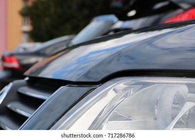 Close up car parked in a parking lot with other cars in the background