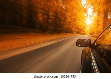 Close up of a car speeding on the empty, autum road with copy space