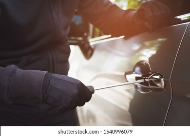 Close up car thief wearing black clothes hand holding screwdriver tamper yank and glove stealing automobile trying door handle to see if vehicle is unlocked  trying to break into. car theft concept.