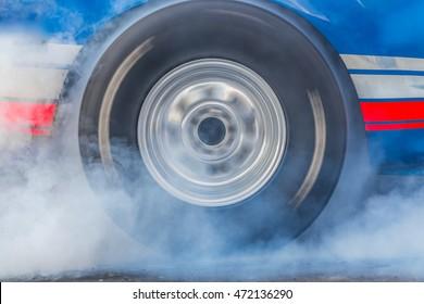 Close up car wheel burnout tire with white smoke