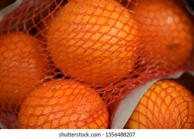Close up of Cara Cara oranges in red mesh bag, as displayed for sale in a grocery store with no posing.  Color is appetizing and real, with no post editing.