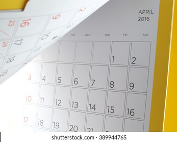 close up cardboard desk calendar with days and dates of April 2016 in grid and yellow edge, reminder monthly business planning or meeting deadline, flip the calendar page
