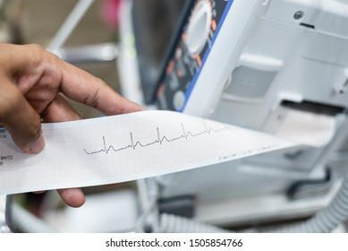 Close up of cardiologist doctor  holding and reading ekg paper print report of heart disease patient in the operating room before operation.Seriously case heart patient monitoring concept.