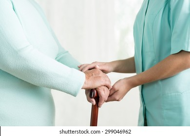 Close up of caregiver holding hand of old female