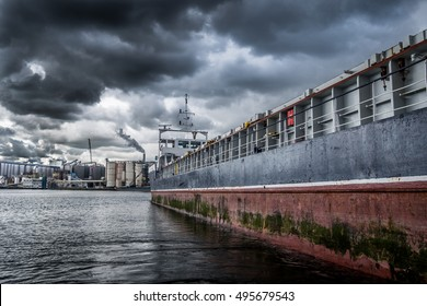 Close up from a cargo ship in bad weather. Factory with silo's at the background.