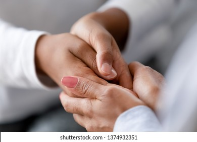 Close up caring African American mother holding child hands, showing love and support, black mum comforting, caressing kid, children protection concept, family enjoying moment together
