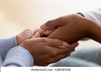 Close up of caring black mom holding child hands showing unconditional love and support, African American mother or nanny comfort kid, caressing, having close intimate moment together