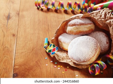Close up Carnival Donuts with Powdered Sugar on Paper with Colored Props on Sides, Placed on Wooden Table.