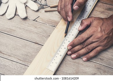 close up carpenter making measurements on the wooden plank
