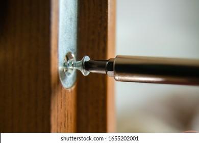 Close up of carpenter repairing door lock. Installing a door handle. Handyman tightening door hinge . Hands of the repairman with a screwdriver. Locksmith screwing bolt into wooden door
