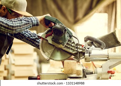 Close up a carpenter in work clothes  doing woodwork in carpentry. small buiness owner cut on wood plank  with circular saw in workshop