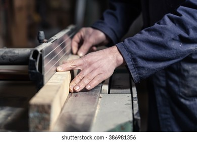 Close up of Carpenter's hands cutting wood with tablesaw in workshop