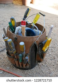 Close up of a carpenter's tool bag sitting over a bucket full of hand tools, sitting on the gravel ground with an orange power lead in the foreground in a boat builders work yard in Victoria Australia