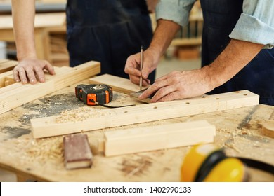 Close up of carpenters workstation with senior man measuring wood, copy space