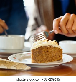 Close up of carrot cake on plate with person holding fork in background