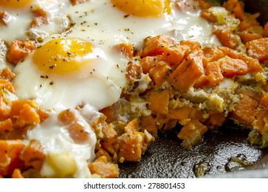Close up of cast iron skillet filled with fried eggs and sweet potato hash