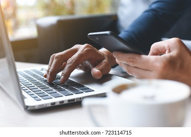 Close up of casual man or freelancer working on laptop computer, holding mobile smart phone with coffee on table in coffee shop or cafe, working from cafe, casual business, startup business concept.