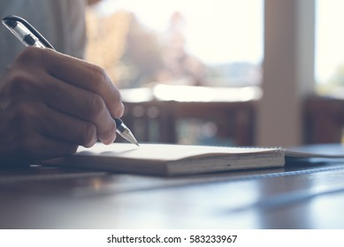 Close up of casual man writing on paper notebook or old diary at home
