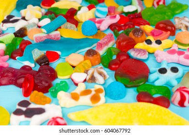 Close up of cattered tasty bright chewing sweets and jelly candies on wooden turquoise board