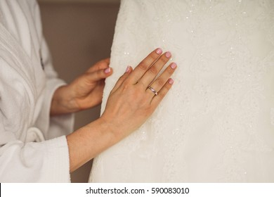 Close up of caucasian bride touch her wedding dress. Engagement ring on woman's finger.