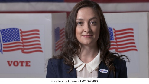 "Close up Caucasian businesswoman in smart jacket wearing ""I Voted"" sticker in front of polling booths with US flag on wall"