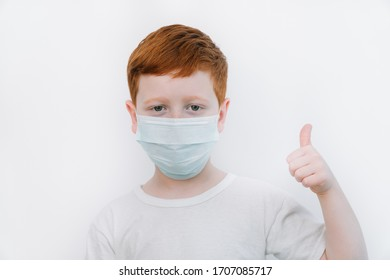 Close up of caucasian little boy in blue protective mask. Little red-haired boy shows instructions on how to not get coronavirus