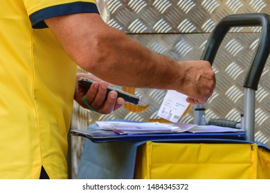 Close up of caucasian man reading code bars on mail with a hand held portable electronic device in the street before distribution.