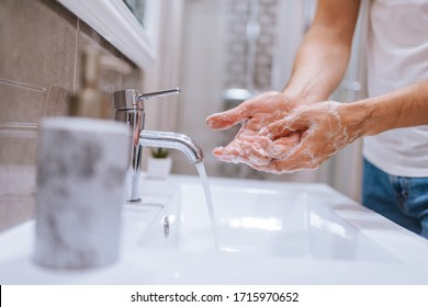 Close up of caucasian man washes his hands in the bathroom. COVID - 19 prevention