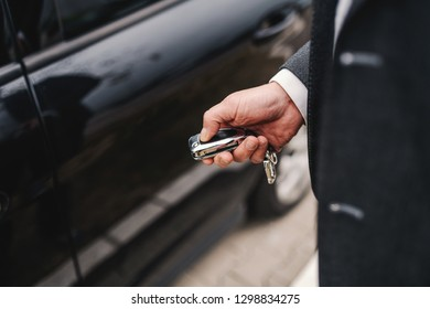 Close up of Caucasian middle aged man in suit locking his car.
