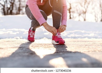 Close up of Caucasian woman crouching and adjusting sneaker before running outdoors. Wintertime, snow all around.