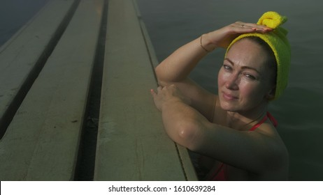 Close up caucasian woman in a swim in hot saline mineral water bath at a traditional spa outdoor with soft magic pink lighting and steam. Girl relaxing spring in hot geothermal spa pool is towel cap.