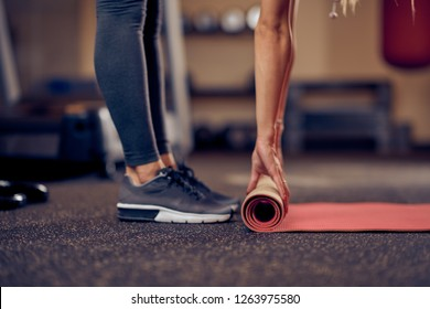 Close up of Caucasian woman unwinding the mat and preparing for exercises. Gym interior. healthy lifestyle concept.