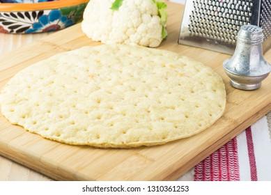 Close up of cauliflower pizza crust on a cutting board.