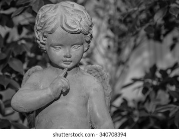 close up cement cherub doll in garden. Aged monochrome photo. Black and white.
