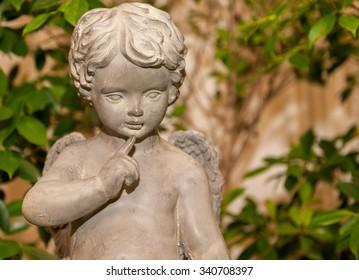 close up cement cherub doll in garden