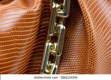 Close up of the chain of a ladies handbag. Leather bag with gold string. Fashion concept  Luxury leather woman's handbag. Golden cord of a fashionable bag. detailed Top view