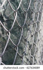 Close up of chain link fence with green fabric screen