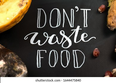 Close up of a chalkboard with Don't waste food lettering and rotten fruits. Selective focus. Concept of stop wasting food