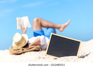 Close up of a chalkboard on the sand of a beach, background happy smiling caucasian tourist asian young man relax and reading book. Summer and Travel Concept.