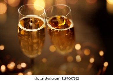 Close up champagne glasses on festive dark background with golden bokeh
