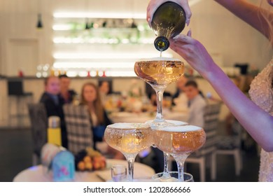 Close up of champagne tower filled by a bride before wedding guests' eyes. The sight of pouring the pyramid of champagne glasses at wedding celebration. Bride makes a champagne cascade show. Drinks