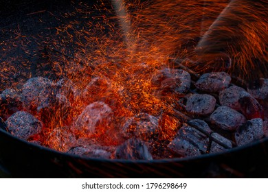 Close up of charcoal smoldering with sparks in grill - starting a fire for outdoor cooking