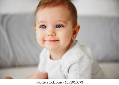 Close up of charming baby sitting on bed