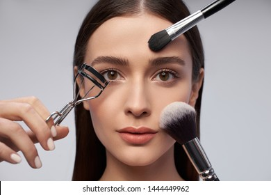 Close up of charming lady looking at camera with serious expression with tweezers for curling eyelashes and makeup brushes near face
