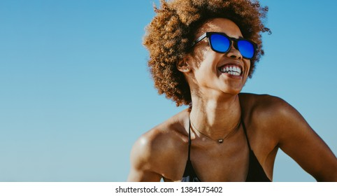 Close up of cheerful african woman in sunglasses looking away and smiling. Young female in bikini having fun outdoors on summer vacation.
