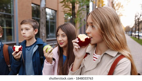 Close up of cheerful Caucasian school students standing outdoors and eating apples. Boys and girls schoolmates in good mood having snack at lunch near school in good mood. Food concept