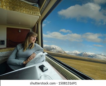 CLOSE UP Cheerful Caucasian woman looks through the window of her sleeper train cabin as she travels across the Tibetan plains. Happy girl daydreaming while travelling down the Trans-Himalayan Railway