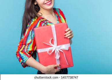 Close up of cheerful good looking young brunette woman holding a red gift box in her hands, but against a blue background. Concept holidays and presents