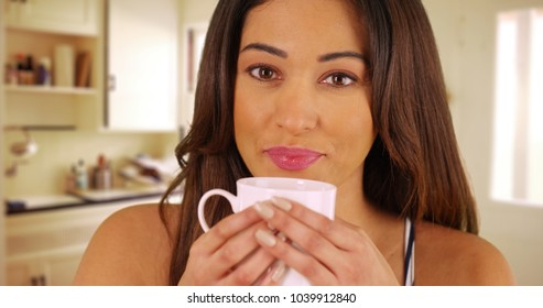 Close up of cheerful Latina female drinking from coffee mug inside kitchen